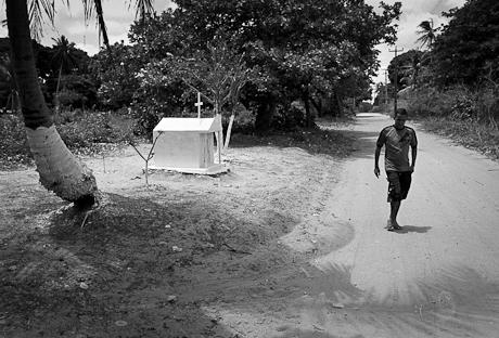 Elizeu walks past road-side shrine. Patacas, Aquiraz - CE, Brazil. 2008.