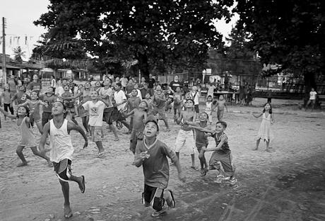 Children run after falling candy. Patacas, Aquiraz - CE, Brazil. 2006.