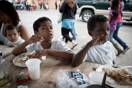 The boys eating after church at a street vendor.  Guayaquil, Ecuador. 2011.