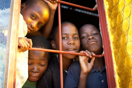 Children peer out the window. Swaziland. 2005.